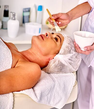 35 40 years old: Woman with close up middle-aged take facial and neck clay mask in spa salon.