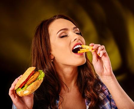 comida chatarra: La muchacha come con apetito de comida rápida hamburguesa grande y patatas fritas.
