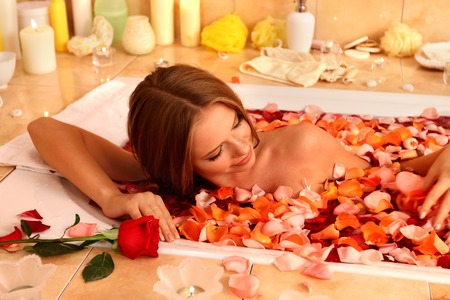 sauna nackt: Young beautiful woman luxuriating with rose petals hot bath in spa saloon.