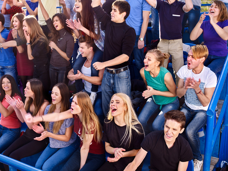 grandstand: Large group sport fans clapping and singing on tribunes. Group people. Stock Photo