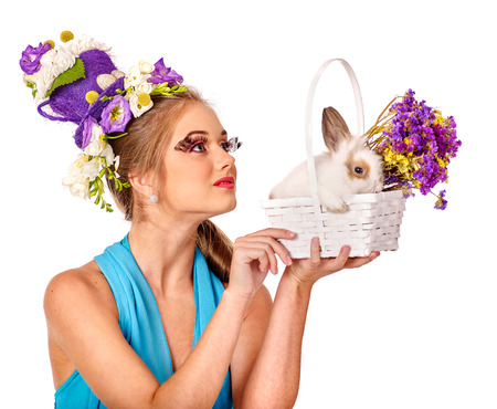 cute lady: Fashion woman look up in easter style holding bunny and flowers. Isolated.