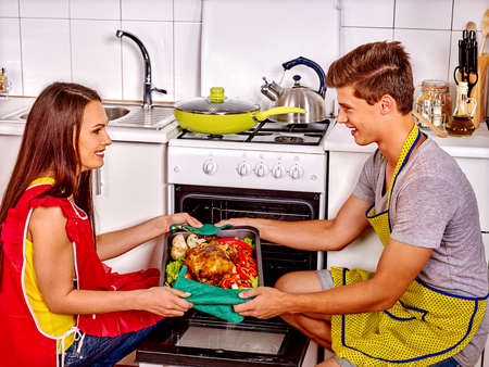 hot guy: Young family cooking chicken at kitchen. Man in red apron. Stock Photo