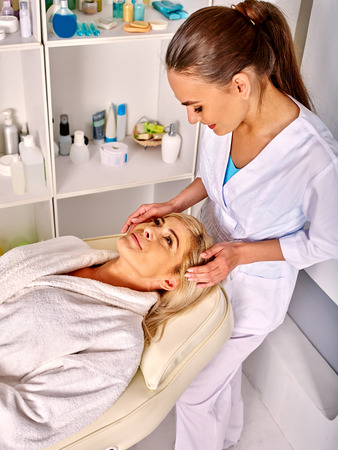 35 40 years old: Woman middle-aged take face and neck massage in spa salon. Two people.