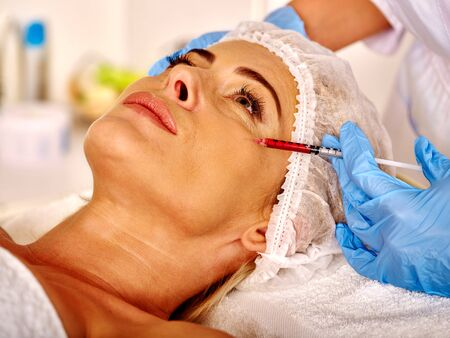 35 40 years old: Woman look up middle-aged in spa salon with beautician. Beauty female giving botox injections.