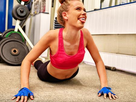 push ups: Fun young woman doing some push ups in gym.