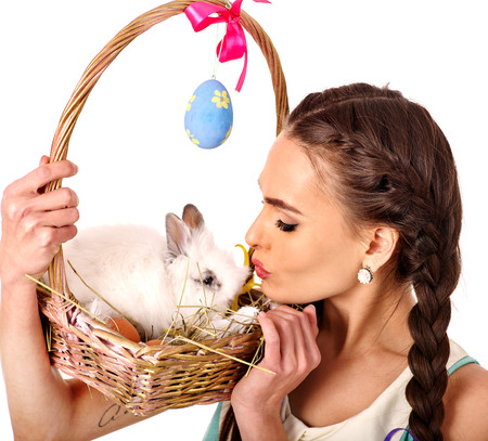 cute lady: Woman in easter style kissing rabbit in basket with bow. Isolated.