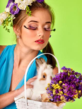 pestaÑas postizas: Mujer con las pestañas falsas y flores en el pelo la celebración de conejo de Pascua. fondo verde.
