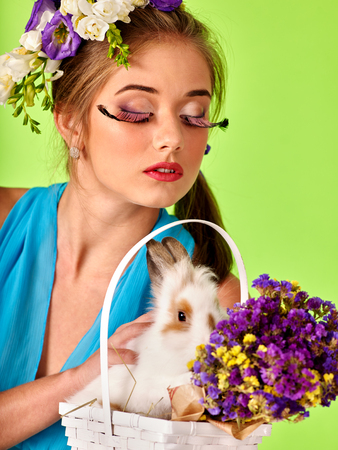 Woman with false eyelashes and flowers in hair holding easter bunny. Green background.