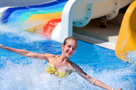 tenager: Happt teen girl on water slide at aquapark. Summer holiday. Stock Photo
