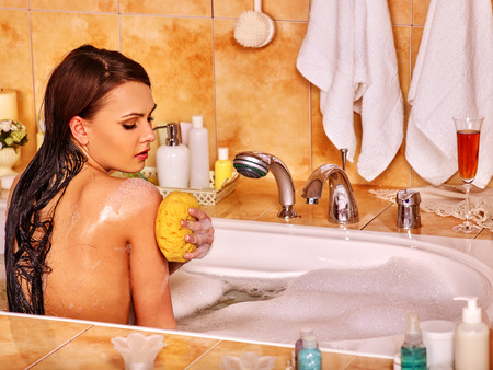 vaporarium: Young woman take bubble  bath at home. Woman washing her shoulder.