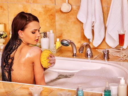 vaporarium: Young woman take bubble  bath at home. Woman washing her shoulder.