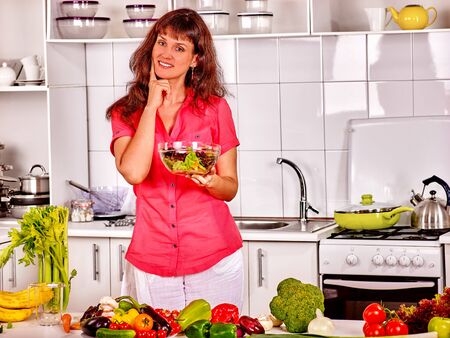 red tshirt: Happy woman preparing and eating salad at kitchen. Red t-shirt.