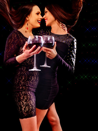 black lesbian: Lesbian women drinking red wine and dancing on nightclub on black background.