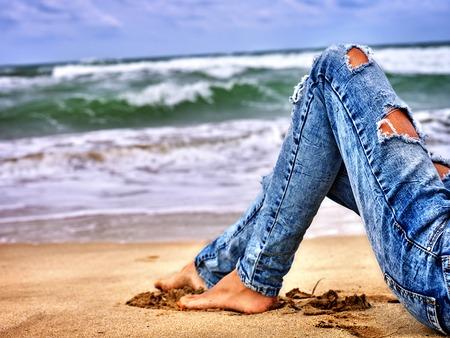 in jeans: mar chica del verano. Mujer que se sienta en la costa cerca del océano con olas. pata de perro caliente que desgasta los pantalones vaqueros con agujeros autofoto.