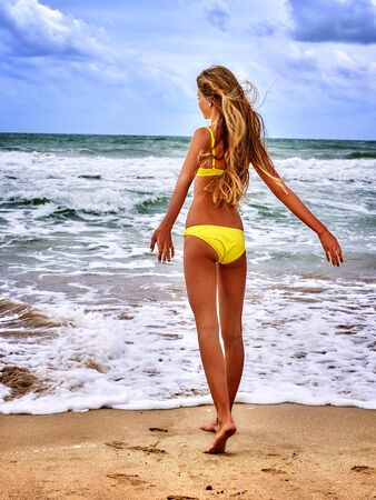Summer girl sea.  Woman in  yellow swimsuit on beach near ocean with waves and horizon. Back view.