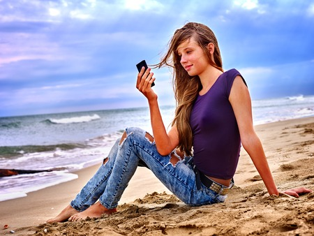 first love: Girl with mobile phone sitting on sand near sea and blue sky. First love.