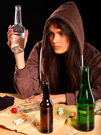 dipsomania: Drunk girl in hood keeps bottle of alcohol. Soccial issue alcoholism.