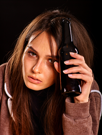 alone girl: Drunk girl keeps bottle of alcohol. Soccial issue addict alcoholism. Black background.