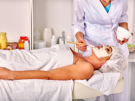 35 40 years old: Lying woman wearing medical hat middle-aged take facial and neck clay mask in spa salon.