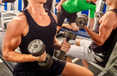 simulator: Group of unrecognizable men working on simulator his body at gym. Stock Photo