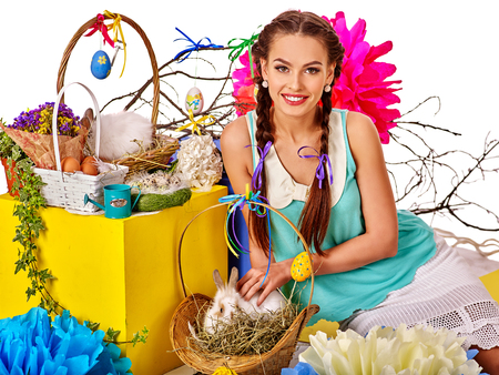 caress: Woman with pigtails in easter style caress white rabbit  in basket.