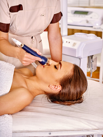 sound therapist: Head of young woman lying with closed eyes receiving electric ultrusound facial massage at beauty salon.