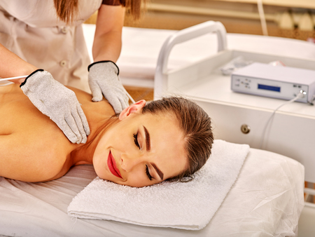 sound therapist: Young woman  with closed eyes lying on stomach receiving electric massage at beauty salon. Beautician wearing electricity gloves. In room is device for hardware cosmetology.