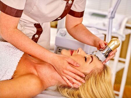 rf: Young woman with blond long hair receiving electroporation  facial therapy at beauty salon.