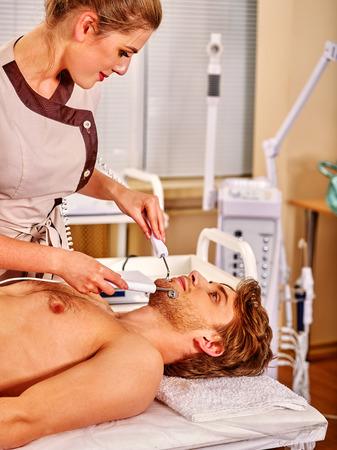 sound therapist: Man enjoying electric facial peeling hydradermie at beauty salon. Young beautiful beautician.