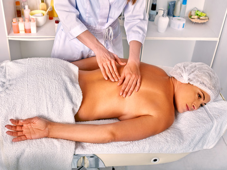35 40 years old: Woman middle-aged in medicine hat take relax back massage in spa salon with young beautician. Stock Photo