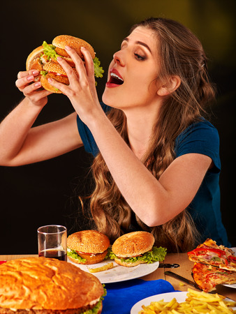 Girl eats with appetite fastfood big hamburger and fried potatoes . Stock Photo