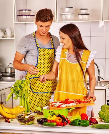young woman smiling: Just married couple cooking vegetable dinner at home kitchen. Stock Photo