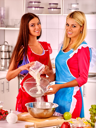 pours: Young women  baking cookies in oven. Woman pours flour.