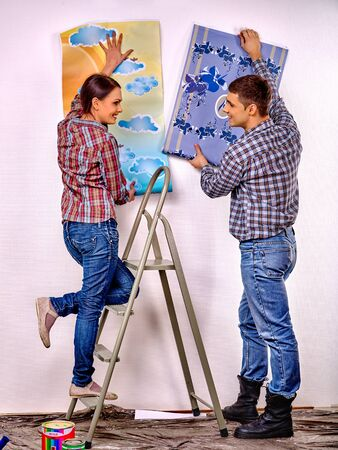 stepladder: Happy family glues wallpaper on  stepladder at home.
