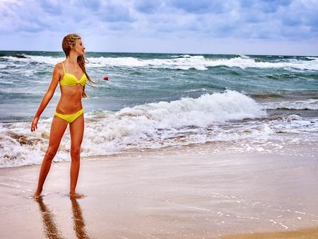 petite fille maillot de bain: fille Summer mer. Femme, Porter, maillot jaune sur la plage près de l'océan avec des vagues.