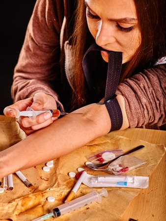tourniquet: Female drug addict with  tourniquet on his arm and  syringe. She puts herself an injection. Stock Photo