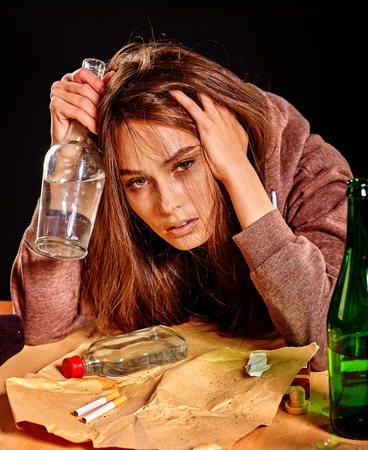 dipsomania: Girl in depression holds his head and drinking alcohol cigarettes in solitude. Stock Photo
