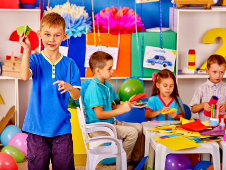 colored paper: Group kids with colored paper on table in start school.