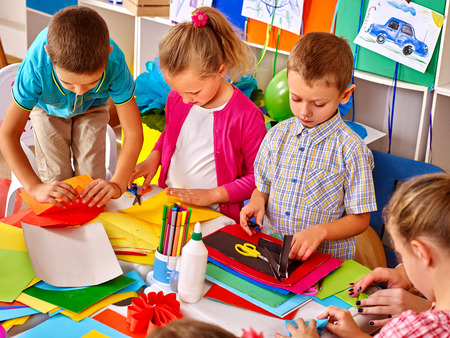nursery education: Group kids holding colored paper on table in preschooler. Stock Photo