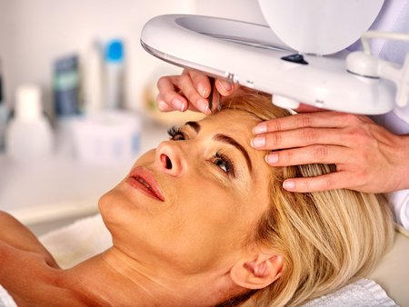 tweezing eyebrow: Woman middle-aged in spa salon with young beautician. Tweezing eyebrow by beautician. Aesthetic medicine.