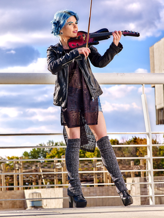 concert background: Music street performers slim girl violinist with blue hair playing  aganist sky with clouds outdoor. Urban landscape.