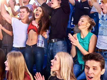 spectator: Sport fans clapping and singing on tribunes. Group people on spring outdoor.