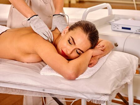 sound therapist: Woman  receiving electric back massage at beauty salon. Beautician wearing electricity gloves. In room is device for hardware cosmetology. Modern technologies in beauty. Stock Photo