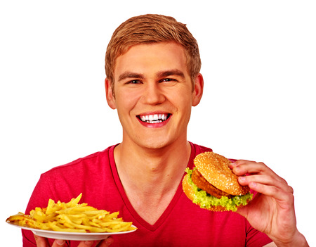 fried food: Young man eating fast food big hamburger and fried potatoes. Fastfood concept. Stock Photo