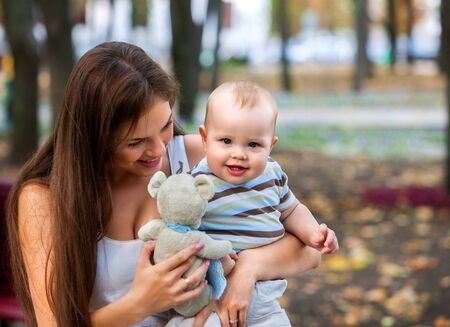 family day: Happy mother and her baby-boy on hands play keeps teady bear toy outdoors in park.