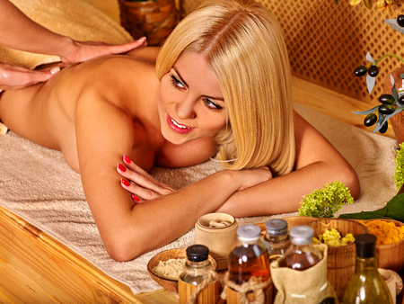 masseuse: Blond woman with beautiful long hair getting massage in tropical spa. Visible hand masseuse.