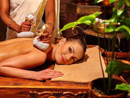 panchakarma: Woman having ayurvedic massage with pouch of rice. Cultural traditions of India.