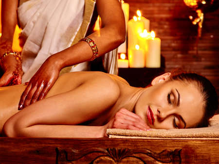 window treatments: Young woman having oil Ayurveda spa treatment. Lighting candles.