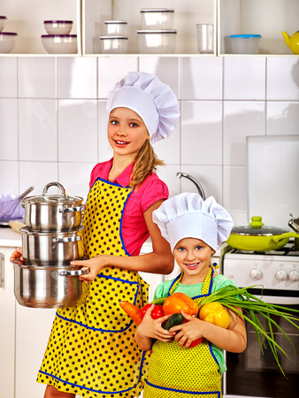 vegetable cook: Child in cooking hat holding vegetable at kitchen. Children learn to cook