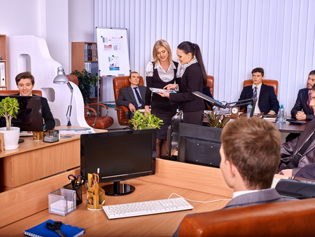 consulted: Happy group business people in office. Two business women are consulted. Stock Photo